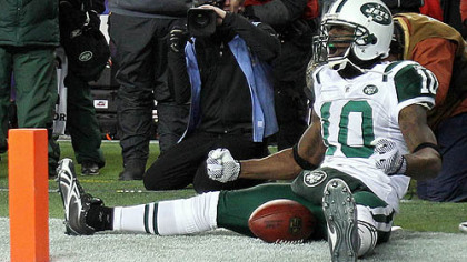 Jets receiver Santonio Holmes  celebrates his fourth-quarter touchdown against the Patriots Sunday in Foxborough, Mass.