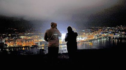 A man and a woman look out over a lit Heinz Field hours before the start of the Winter Classic from Mt. Washington last night.