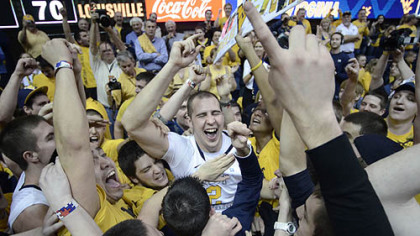 West Virginia's Cam Thoroughman, center, celebrates with fans following a 72-70 win against Louisville today in Morgantown, W.Va.