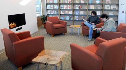 Ruth Bogdan, left, and her mother, Ruth Collura, sit in the reading area around the fireplace in the new, $2.5 million Bridgeville library. They were the first in the door when it opened Monday.
