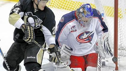 Matt Cooke, left, attempts to backhand a rebound off Columbus Blue Jackets goalie Steve Mason Tuesday