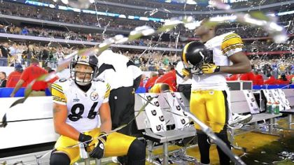 Steelers Hines Ward and Antonio Brown sit on the sidelines as confetti falls around them marking the Packers' victory in Super Bowl XLV.