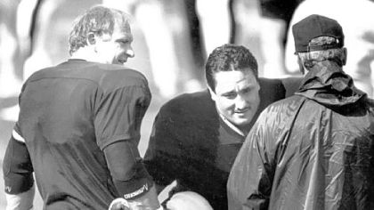 Mike Webster helps replacement player Ben Lawrence stretch before a workout in the 1987 strike camp in Johnstown.