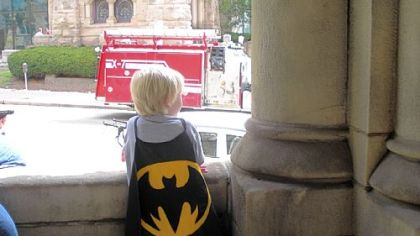 Jake Schraven, 5, in a handmade Batman cape, watches the filming.