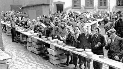 European refugees eat at a dispersal point at the former German political prison at Ansalt on March 19, 1945.