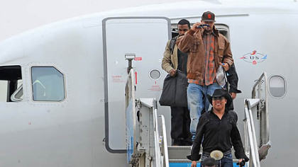 Hines Ward wears a cowboy hat and large belt buckle as he makes his way off the jet.