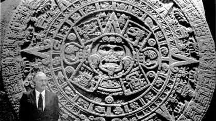 Carlos Fuentes stands next to the Aztec calendar in the National Museum of Anthropology in Mexico City.