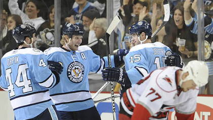 Penguins forward Dustin Jeffrey celebrates a second period goal with teammates Brooks Orpik and Jordan Staal as Hurricanes defenseman Joe Corvo looks down during Saturday&#039;s game at Consol Energy Center.