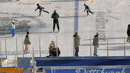 As skaters take to the ice for the last time, Heinz Field workers dismantle the on-field rink Sunday morning after the NHL Winter Classic.