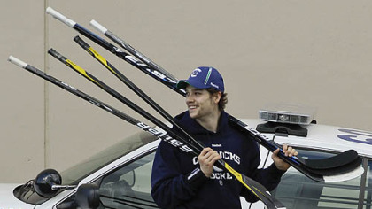 Vancouver Canucks left wing Mason Raymond carries sticks as he arrives at practice for the NHL Stanley Cup Finals, Friday, June 3, 2011, in Vancouver, British Columbia. The Canucks host the Boston Bruins in Game 2 of the best-of-seven games series on tonight. The Canucks lead 1-0.