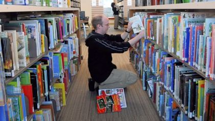 Ed Wolf, a clerk at Bridgeville Public Library, returns books to the shelves in the new, $2.5 million library, which opened Monday on McMillan Street.