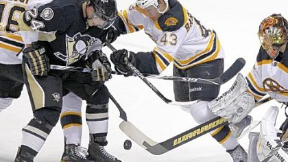 Mt. Lebanon native and Boston Bruins defenseman Matt Bartkowski, right, battles the Penguins' Matt Cooke for the puck in Monday night's game at the Consol Energy Center. Bartkowski made his NHL debut in the contest, which the Bruins won, 4-2.