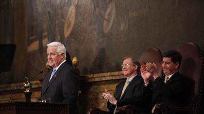 Gov. Tom Corbett talks about his 2011-2012 budget proposal before the state Legislature. Behind him are Speaker of House, Rep. Sam Smith, R-Jefferson, left, and Lt. Gov. Jim Cawley.