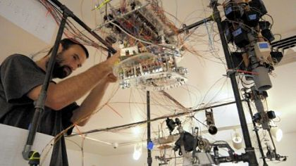 "Adam Shreckhise assembles his installation art, ""POM (Portrait of the Artist as a Machine),"" a complicated maze of circuits and machine parts that will create its own art when completed. Installations are in progress for the 2011 Pittsburgh Biennial at Pittsburgh Center for the Arts, Shadyside."