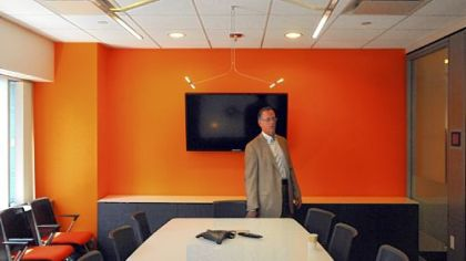 "Gary Saulson, director of corporate real estate for PNC Financial Services Group, in the ""Frontal Cortex"" conference room on the 19th floor of Two PNC Plaza. It uses LED lighting from above, and you can write on the surface of the table, which lights up and tilts up like a blackboard."