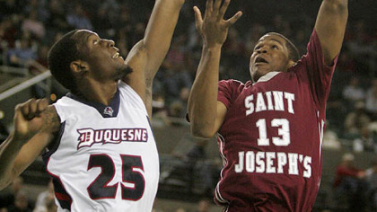 Saint Joseph's Ronald Roberts takes a shot as Duquesne's Damian Saunders defends in the second half of yesterday's Atlantic 10 tournament game in Atlantic City, N.J.