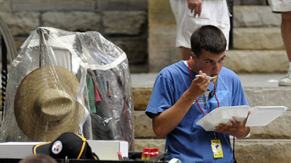 A crew member eats lunch next to a wardrobe rack outside Trinity Cathedral, Downtown, during filming on Aug. 10.