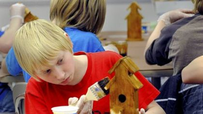 Anthony Raynes, 11, works on his birdhouse project during the South Elementary after-school boys club Gladiator Guys activities.
