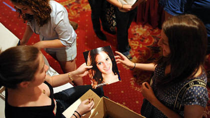 "Katharine Bodner, 19, of Jefferson Hills, right, hands a profile picture over to Pittsburgh Film Office intern Claire Dempsey on Sunday as hundreds of people attend a casting session for ""The Dark Knight Rises"" at the Omni William Penn hotel, Downtown."