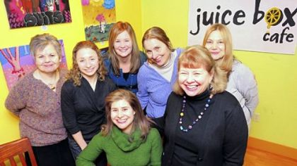Rebecca Gilbert, seated center, with her mom, Shandel, right, and other diners at the Juice Box Cafe in Shadyside.