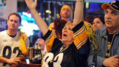 June Hough Repic raises her arms when the Steelers score.