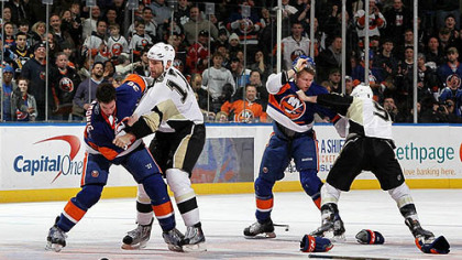 Islanders defenseman Travis Hamonic fights Penguins forard Mike Rupp (left) of as Islanders forward Josh Bailey battles Pascal Dupuis during the second period of Friday&#039;s game at Nassau Coliseum.