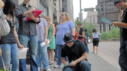 Some of the many people hoping to be extras in the next Batman movie, being filmed in part in Pittsburgh, fill out forms while waiting in the blocks-long line Downtown. Some waited as long as four hours for a shot at a spot in the film.