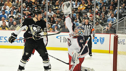 Blue Jackets goaltender Steve Mason reaches up to snag the puck off a shot as Penguins forward Eric Tangradi looks for a rebound during Tuesday's game at Consol Energy Center.