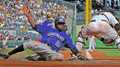 The Rockies' Dexter Fowler scores against the late tag from catcher Ryan Doumit Sunday at PNC Park.