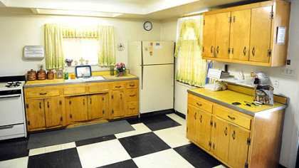 The kitchen has pine cabinetry and Formica counters installed in 1952, when the ceiling was lowered. There's a large pantry behind an elegant wood door.
