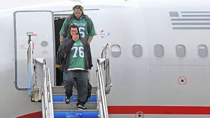 Chris Kemoeatu, foreground, and the rest of the offensive linemen -- all sporting Flozell Adams throwback jerseys from Michigan State -- exit the plane at Dallas-Fort Worth International Airport Monday. The jerseys were a tribute to Adams.