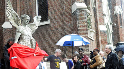 Artist James Simon, left, unwraps his sculpture of St. Michael as a memorial to three slain Pittsburgh police officers following a memorial Mass at St. Joseph Church, Bloomfield.