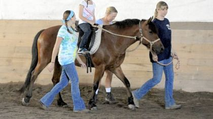 Abby Langer, 8, of Irwin rides on 6-year-old Starlight with help from Stacy Shirer, Pam Burkland and Jennifer Harbaugh at Nickers 'n Neighs.