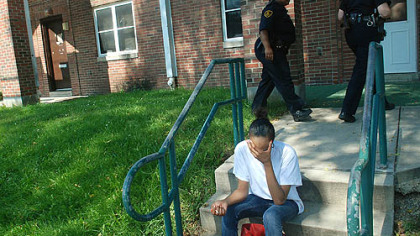 Kendra Jackson, who said she is a sister of the shooting victim, sits on a stoop on Chauncey Drive on Monday as police officers search for information.