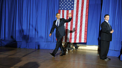 President Obama waves to the audience as he enters the hall to give a speech at the IBEW building on the South Side.