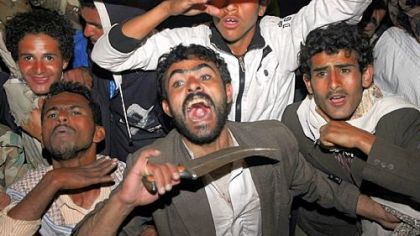 Yemeni anti-government protesters react Wednesday to the announcement that President Ali Abdullah Saleh would reliquish his office after 33 years in power.