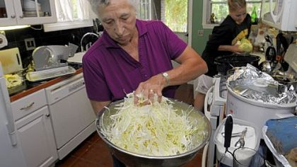Freda Vogelsberger mixes in the salt. Three tablespoons of canning salt to 5 pounds of cabbage is a good ratio.   Dana Tabay, of New Brighton, cuts cabbage in the background.