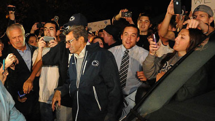 A large group of students and others surround Penn State football head coach Joe Paterno at his home.