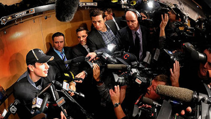Sidney Crosby is besieged by the media at his locker after workouts this morning at the Consol.