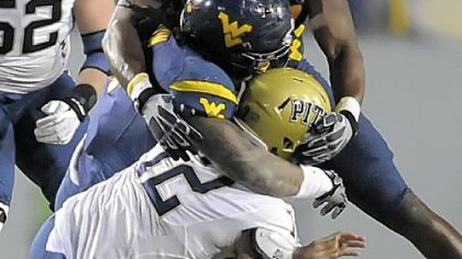West Virginia&#039;s Bruce Irvin and Will Clarke sack Pitt&#039;s Tino Sunseri in the fourth quarter Friday.