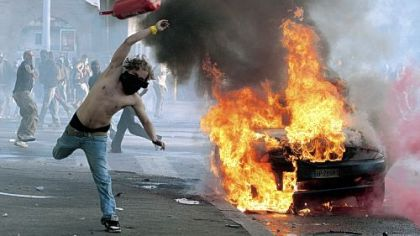 A protestor hurls a canister towards police next to a burning car Saturday in Rome. Protesters smashed shop windows and torched cars as violence broke out during a demonstration in the Italian capital, part of worldwide protests against corporate greed and austerity measures, entitled Occupy Wall Street.