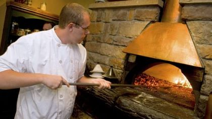 Chef Tom Wurst tends to the wood-burning oven, a centerpiece of the kitchen at Bado's Cucina in Peters.