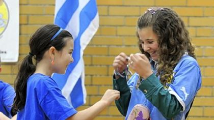 Courtney Walsh, left, a fifth-grader at Howe Elementary in Mt. Lebanon, waits for Valentina &quot;Vale&quot; Fontora of Uruguay to tie on a friendship bracelet.
