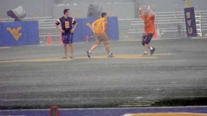 Fans dance in heavy rain at Mountaineer Field in the first of two weather delays at the West Virginia-Marshall game Sunday in Morgantown, W.Va.