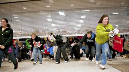 Black Friday shoppers duck under the opening door of a Sears store at Simon Property Group Inc.''s Great Lakes Mall in Mentor, Ohio, U.S., on Friday, Nov. 25, 2011. Black Friday, traditionally the biggest U.S. shopping day of the year, got off to its earliest start ever as retailers tried to woo shoppers with discounts and early store openings.