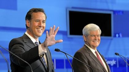 Republican presidential candidate former Pennsylvania Sen. Rick Santorum, left, waves to a member of the audience as former House Speaker Newt Gingrich looks on.
