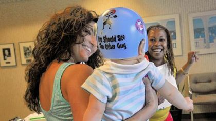 Jocelyn Corcoran (left) and April Blue, who works at Union Orthotics & Prosthetics, play with Jocelyn's son, Braylon, who wears a helmet to help correct a flat spot on his head.