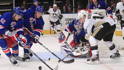 New York Rangers center Artem Anisimov (42) and Ryan McDonagh (27)  help Rangers goalie Henrik Lundqvist defend the goal as Penguins' Chris Kunitz (14) looks on.