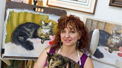 Bernadette Kazmarski, an animal portrait artist who created &quot;Great Rescues,&quot; a calendar that features portraits of cats, in her home studio in Carnegie with her 19-year-old cat, Cookie.