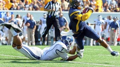 West Virginia receiver Tavon Austin tries to elude Connecticut defender Dwayne Gratz in the first half Saturday at Mountaineer Field in Morgantown, W.Va